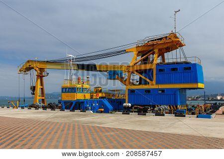 Sea floating self-propelled crane near the pier.