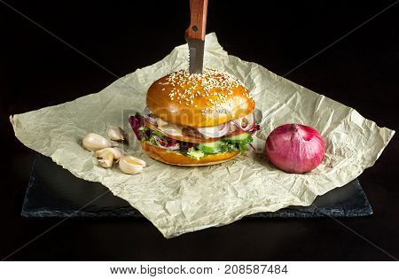Hamburger with garlic is on kraft paper. Nearby is the head of a red onion. Behind the black background.