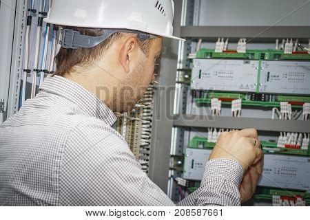Engineer mounts controller for process automation in control cabinet. Electrician in white helmet adjusts tech box of industrial automation