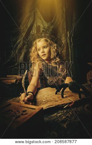 Beautiful charming little witch conjures in her lair. Halloween.