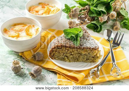 Delicious homemade poppy pie and creamy dessert with apricots. Desserts on yellow napkin mint and dry poppy capsule with seeds on table