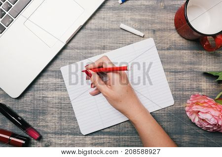 Office table desk, Flat lay. Workspace with flowers laptop red cup lipstick on wooden background. Woman hand writing in a notebook