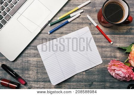 Office table desk, Flat lay. Workspace with flowers laptop red cup lipstick on wooden background.