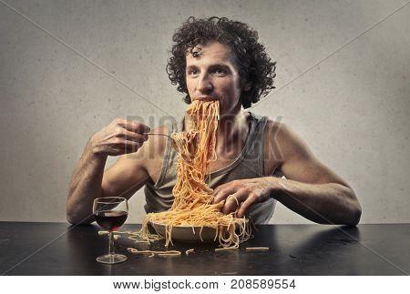 Greedy man eating pasta