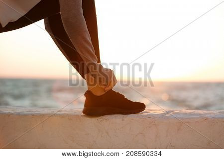 Cropped photo of sport woman tying shoelace at the seaside