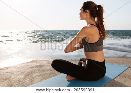 Charming young woman practicing yoga at the seaside