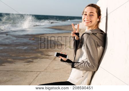 Close-up photo of happy sport woman showing peace sign, looking at camera while listening to music