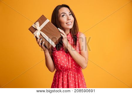Intrigued runette woman in dress holding gift and looking up over yellow background