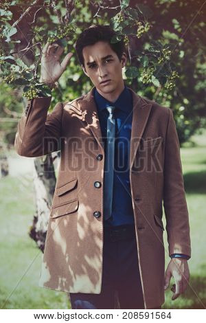Portrait of an elegant young man posing in business clothes in a summer park. Outdoor fashion. Business style.
