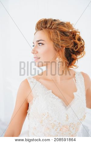 Magnificent bride woman in beautiful pale apricot wedding dress in luxurious apartments.