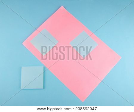 Blank blue paper stickers on a pink and blue paper background (minimal concept top view)