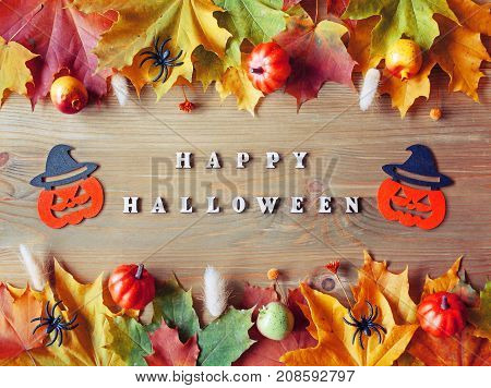 Halloween background. Happy Halloween letters with seasonal leaves and smiling jack decorations as symbols of Halloween on the wooden background. Flat lay top view. Happy Halloween concept
