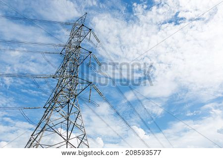 High voltage tower with background of cloudy sky.