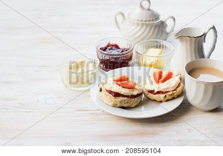 English scones with butter, jam and cream, tea with milk on the white wooden table, selective focus copy space for text