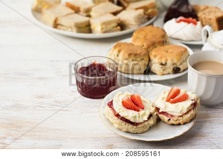 English cream teas, scones with jam and cream, tea with milk, with sandwiches on the back, on the white wooden table, selective focus copy space for text