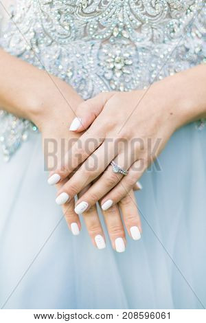 bride hands with wedding ring on the wedding dress