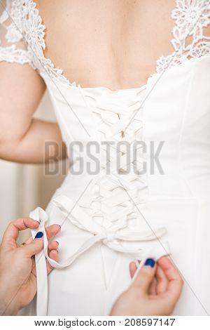 Wedding. Bridesmaid helps the bride to wear wedding dress