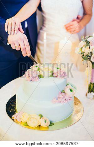 bride and groom hands near wedding cake indoors