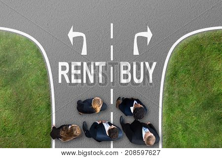 High Angle View Of Businesspeople Standing Near Arrows Showing Rent And Buy Directions