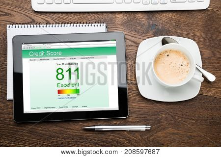 Elevated View Of Digital Tablet Showing Credit Score At Desk With Coffee Cup