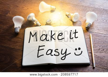 Close-up Of A Make It Easy Text On Notebook With Pencil And Glowing Lightbulb