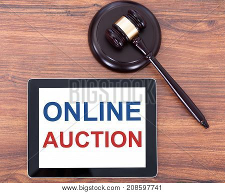 Elevated View Of Online Auction Text On Digital Tablet With Gavel On Wooden Table
