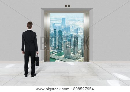 Rear View Of Businessman With Briefcase Looking At Modern Elevator With Opened Door To City