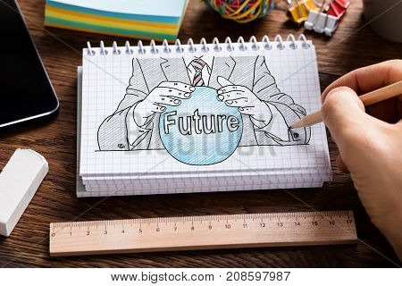 Businessperson's Hand Holding Pencil Drawing Fortune Teller Concept In Spiral Notebook With Stationery
