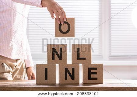 Close-up Of A Person Hand Arranging Blocks With The Text Online Over Wooden Table