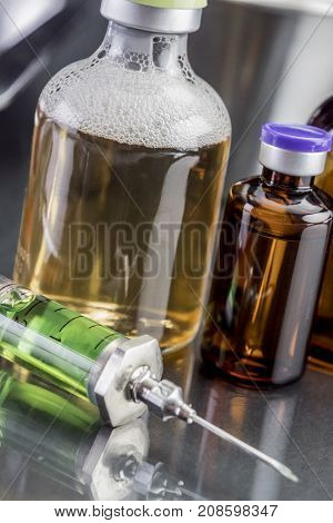 Several vials and syringe in laboratory, conceptual image