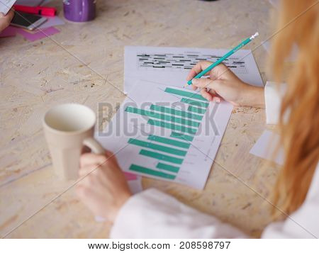 A girl with a coffee and pencil in the other hand looks at the company's work schedule. A businesswoman with paper.