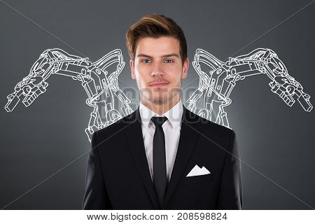 Young Businessman With Robotic Arms On Background