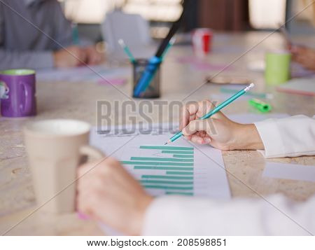 A girl with a coffee and pencil in the other hand looks at the company's work schedule