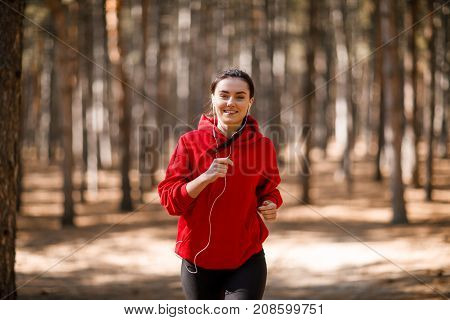 Young brunette athlete in a red sweatshirt is running around in headphones in an autumn forest. Close-up.