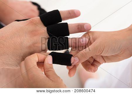High Angle View Of A Doctor Putting Finger Protector Sleeve On Man's Finger In Clinic