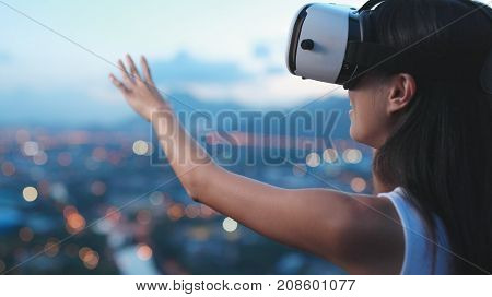 Woman watching with virtual reality device in the sunset
