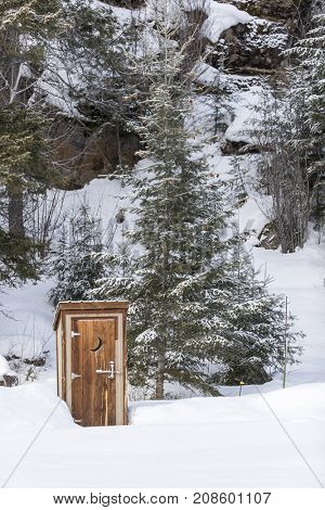An outhouse in a wintry scene