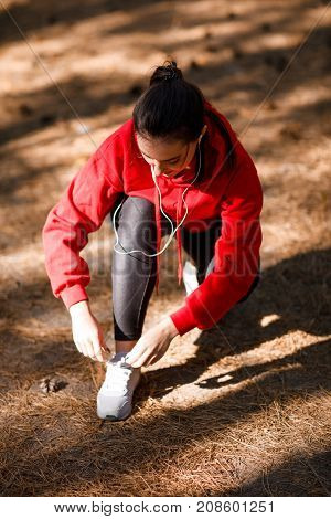 A girl in a red sweatshirt and headphones, tying shoelaces in the forest during training. View from above. Concept photo, close-up.