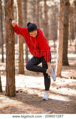A beautiful young girl in a red sweatshirt rests on a tree trunk adjusting her sneaker. In full growth.