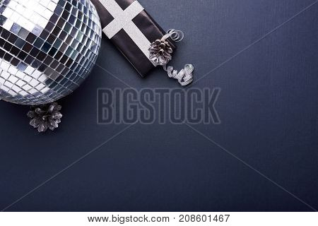 christmas decoration. disco ball, gift box over blue background. top view