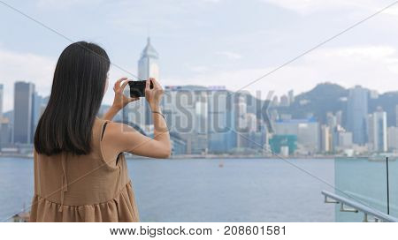 Young Woman taking photo with cellphone in Hong Kong Victoria harbor