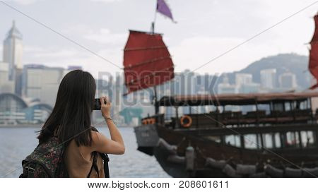 Woman taking photo on cellphone in Hong Kong city