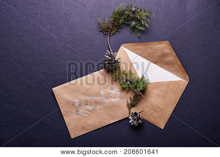 decoration for christmas. browm envelope, 2018 sign, evergreen twig  and pine cone painted in silver over blue background