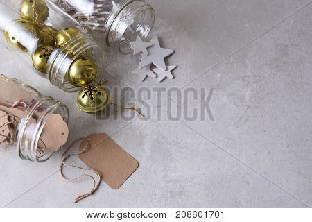 Christmas present wrapping supplies. High angle shot of three mason jars on their side with gift tags, wood stars, and sleigh bells with copy space.