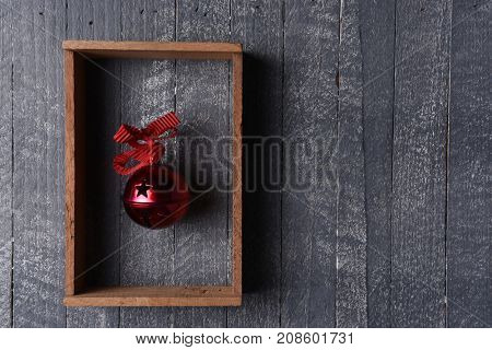 A red jingle bell in a wood frame on gray wood wall with copy space.