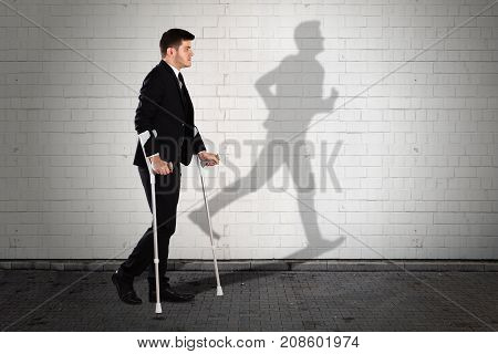 Shadow Of Man Running Formed On Wall With Young Businessman Walking With Crutches On Sidewalk