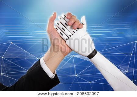 Close-up Of Businessman And Robot Doing Arm Wrestling Over Abstract Background