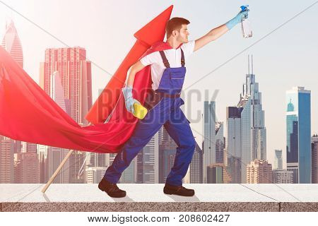 Young Male Janitor In Superhero Costume Flying With Rocket Against City Skyscrapers