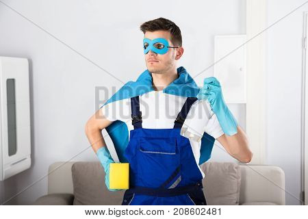 Young Superhero Janitor In Blue Cape Holding Cleaning Equipments