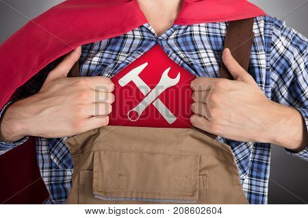 Close-up Of Superhero Handyman Opening Shirt For Showing Worktools Sign
